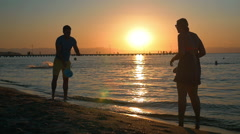 Couple playing tennis on the beach at sunset Stock Footage