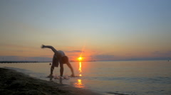 Athlete doing acrobatic tricks on the beach at sunset Stock Footage