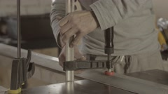 Professional carpenter fix metal balk on wooden board. Making furniture Stock Footage