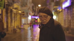 Old man at the center of young passers-by on the street and the city is nothing Stock Footage