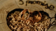 Gold wedding rings on a wooden background decorated for a marriage ceremony Stock Footage
