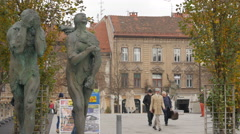 Pedestrians walking on the Butchers' Bridge by the sculptures in Ljubljana Stock Footage