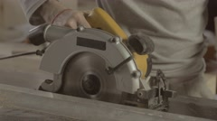 Carpenter careful cut wooden board on straight line of metal balk. Circular saw Stock Footage