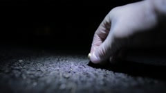 Forensic Officer with gloves picking up bullet shell off floor at night Stock Footage