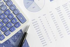 Retirement projections for return and annual inflation with pen and calculator - stock photo