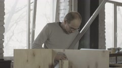 Carpenter search something among woodworking materials. Hold metal balk in hands Stock Footage