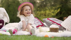 Happy child sits on a meadow around Easter decoration Stock Footage