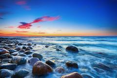 Sunset over the Baltic sea. The pebbly beach in Rozewie. - stock photo