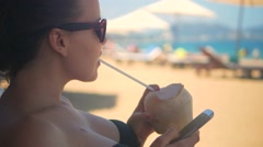 lifestyle relaxing woman using cellphone and drinking a cocktail from a coconut - stock footage
