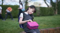 4K Sad little girl alone in schoolyard cheers up when children come to play Stock Footage