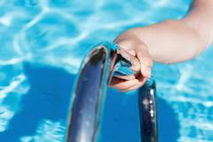 Female's hand holding a handrail in swimming pool - stock photo