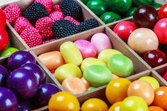Multi colored candy and chewing gum in a wooden box Stock Photos