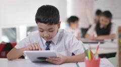 4K Portrait of happy little boy using computer tablet in school classroom Stock Footage