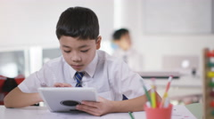 4K Portrait of happy little boy using computer tablet in school classroom Stock Footage