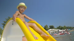Child riding on slider at seaside Stock Footage
