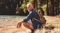 Senior male hiker relaxing by a lake and admiring the view - stock photo