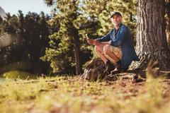 Senior male hiker in forest with a compass Stock Photos