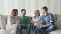 Friends are sitting on the couch at home and talk to each other - stock footage