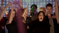 Young people on dancefloor at club putting champagne glasses up in the air Stock Footage