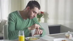 Man is checking his smartwatch while having a lunch and orange juice Stock Footage