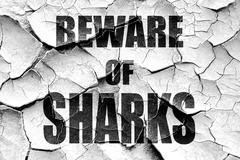 Grunge cracked Beware of sharks sign - stock illustration