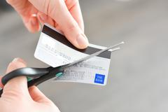 Cutting a credit card suggesting bankruptcy problems Stock Photos