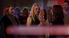 Attractive blond girl in club receives congratulations from friends Stock Footage
