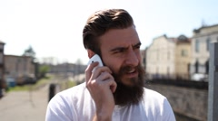 Young man with a beard having a serious conversation at the phone Stock Footage