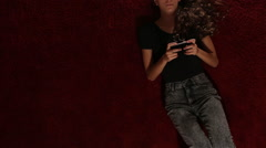 A teenage girl texting on a red carpet, from above - stock footage