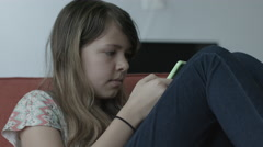 A preteen girl texting on a couch Stock Footage