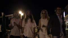 Group of friends walking with music rhythms at night Stock Footage