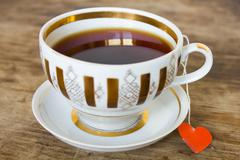 vintage gilded cup of black tea and heart  label - stock photo