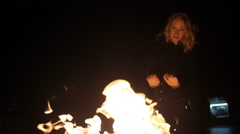 Girl basking hands near the eternal flame at cold winter night Stock Footage