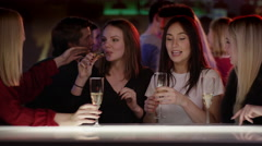 Attractive girls at bar in club with champagne glasses congratulating their f Stock Footage