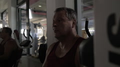 Tired man wiping sweat after workout in the gym - stock footage