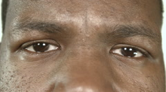 Extreme close up of a black man with angry eyes - stock footage