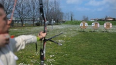 Stock Video Footage of Field archery practice, young archer shooting an arrow at target