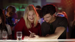 Attractive blond girl at bar in club writing her phone number on hand of good Stock Footage