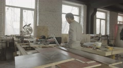 Carpenter measure wooden board by metal balk on table. Process making furniture - stock footage