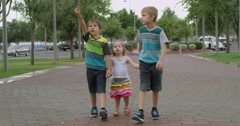 Slow Motion Three Siblings Walking on a Path and Pointing Stock Footage