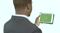 Black businessman looking a tablet or iPad with chroma keyed screen - stock footage