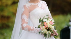 Young beautiful smiling bride holding wedding bouquet of flowers  pose on camera - stock footage