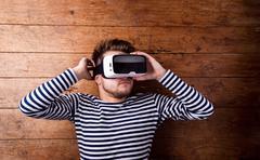 Man wearing virtual reality goggles. Studio shot, wooden backgro Kuvituskuvat