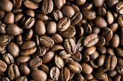 Texture of tasty, rich and fullbody roasted coffee beans. Stock Photos
