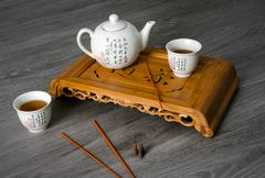 Exotic tea still-life contains teapot, cups, insence and tea sea. Stock Photos