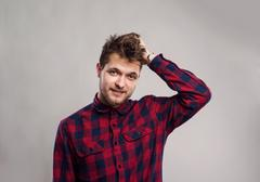 Hipster man in checked shirt smiling, against gray background Stock Photos