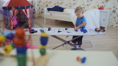 Little curly-headed boy playing with toys in room - stock footage