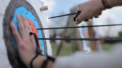 Field archery, young man remove arrows from the target - stock footage