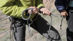 Rock climber tying a special knot for a safety system Stock Footage
