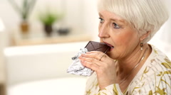 Senior woman takes bite of chocolate bar - stock footage